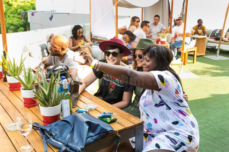 Friends taking a selfie on their phone and generally enjoying a day out at a Food and Wine Fair. Johannesburg, South Africa - October 10 2015: Friends taking a stock photo