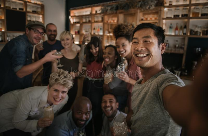 Friends taking selfies while having fun in a bar stock photo