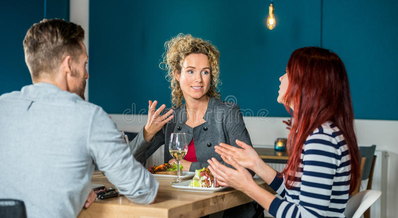 Friends Talking While Having Food At Restaurant. Young women talking to friends while having food at restaurant table royalty free stock photo