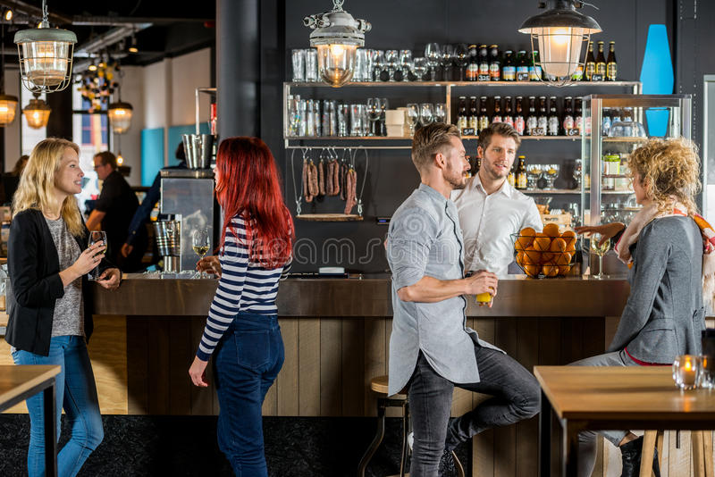 Friends Talking While Having Their Drinks In Bar. Young friends talking while having their drinks at bar counter royalty free stock photography