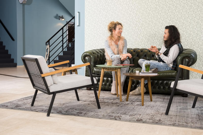 Friends Talking While Sitting On Sofa In Cafe. Young male and female friends talking while sitting on sofa in cafe stock photo