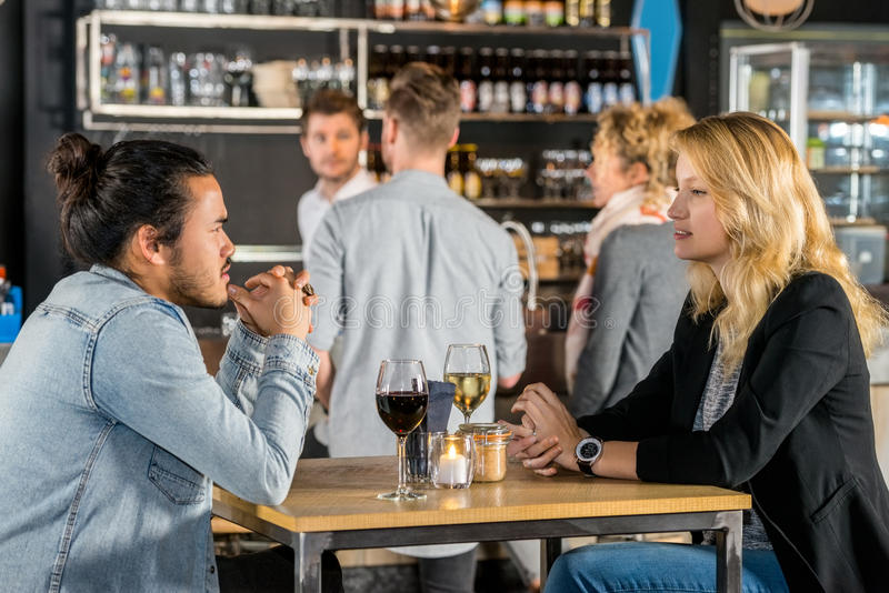 Friends Talking At Table In Bar. Young friends talking with wine glasses on table in bar royalty free stock photography