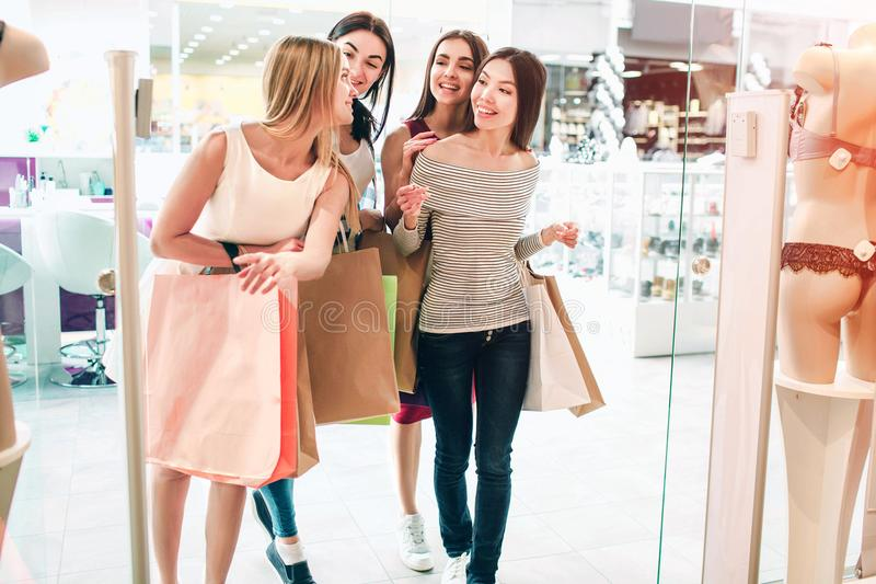 Friends are talking among themselves and walking into lingerie store. They are holding bag. Girls are shopping and stock photos