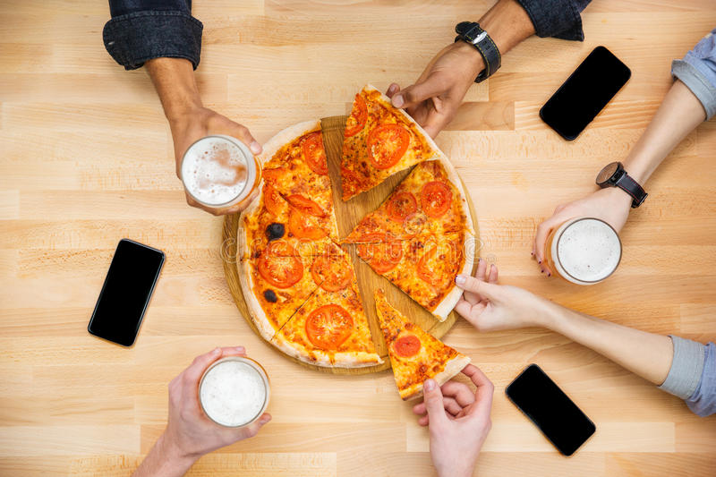 Friends tasting pizza and drinking beer on wooden table stock photography