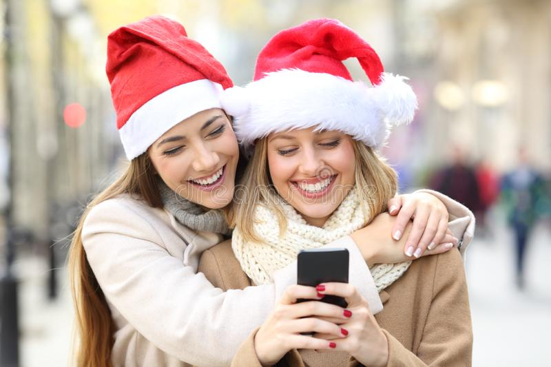 Friends texting on a phone on christmas. Two happy friends wearing santa hats texting on a phone on christmas on the street stock photography