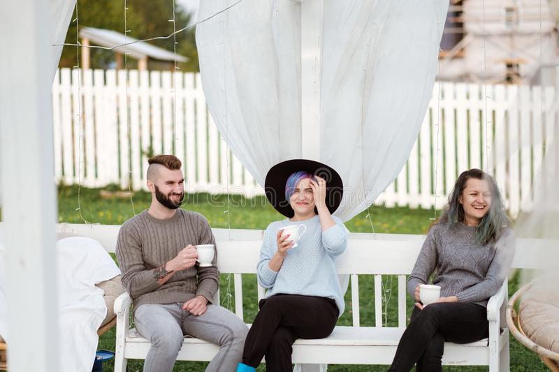 Friends drink tea and have a good time on the terrace of a country house. stock photos