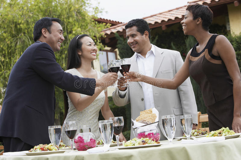 Friends Toasting Wine In Dinner Party royalty free stock photography