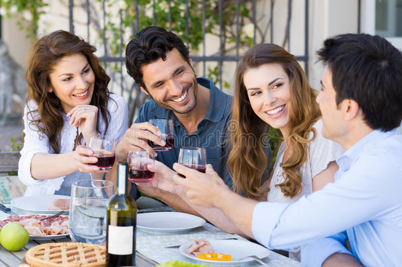 Friends Toasting Wine Glass. Group Of Happy Young Friends Toasting Wine Glass Outdoor While Having Lunch royalty free stock photos