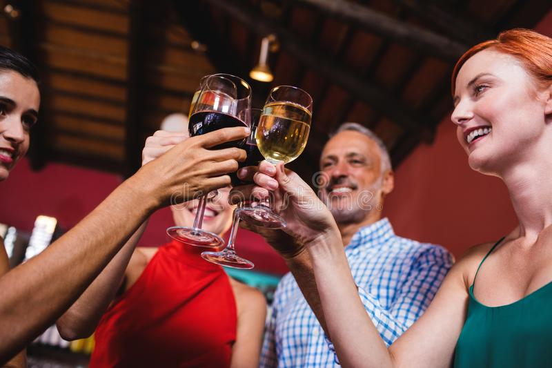 Friends toasting wine glass in night club. Low angle view of friends toasting wine glass in night club royalty free stock photo