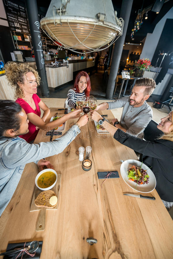Friends Toasting Wineglasses At Table. High angle view of friends toasting wineglasses at restaurant table stock image