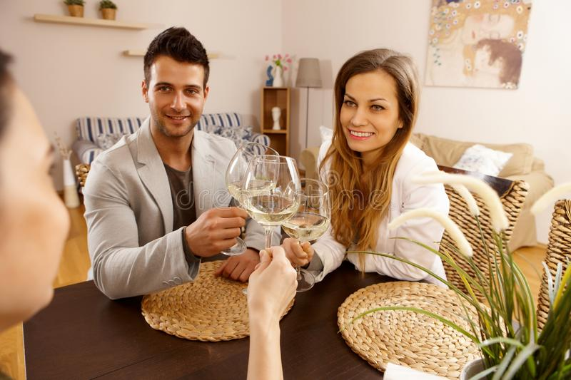 Friends together. Young couple sitting at table, clinking glasses with a friend stock images