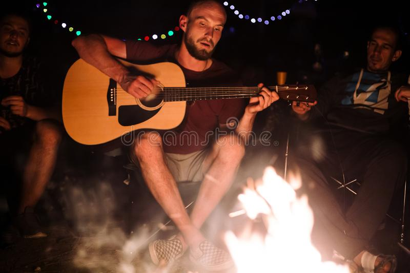 Friends travelers chilling at big bonfire, singing songs and playing guitar at camp in the night forest. Group of people resting stock image
