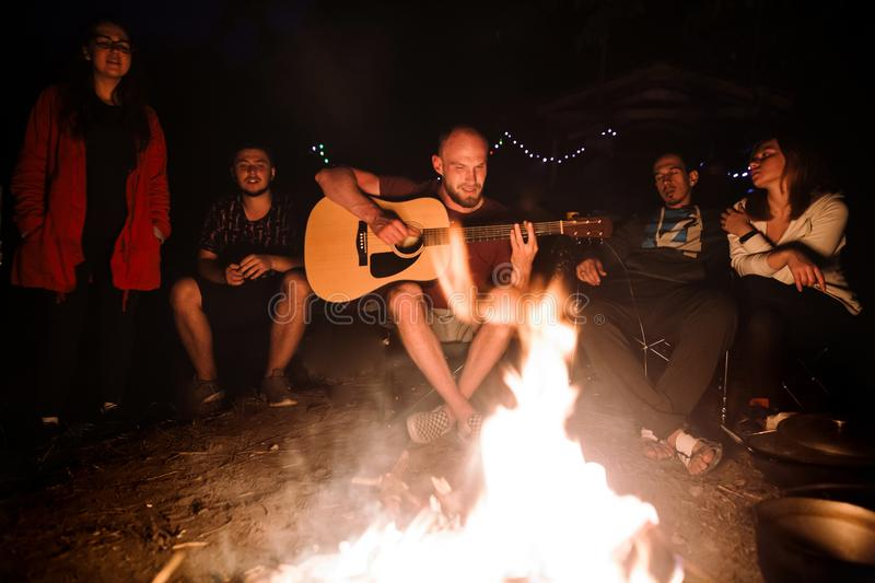 Friends travelers chilling at big bonfire, singing songs and playing guitar at camp in the night forest. Group of people resting royalty free stock image