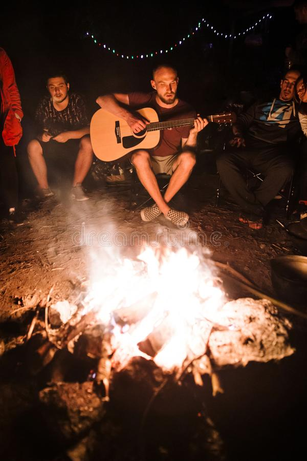Friends travelers chilling at big bonfire, singing songs and playing guitar at camp in the night forest. Group of people resting royalty free stock photography