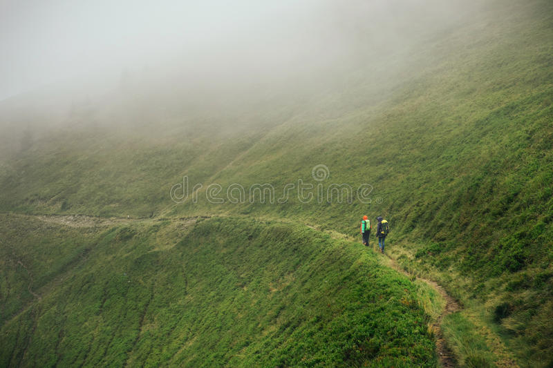 Download Friends Traveling Together In Foggy Mountain Stock Image - Image: 83705815