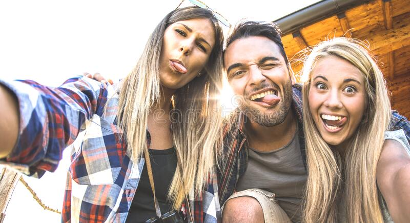 Friends trio taking selfie at trekking excursion - Happy friendship and freedom concept with young millenial people having fun stock image