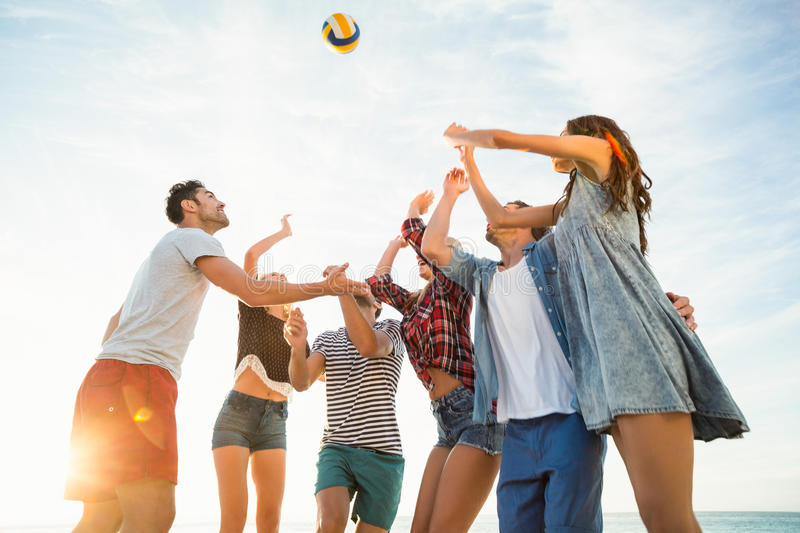 Friends trying to catch volley ball royalty free stock photography