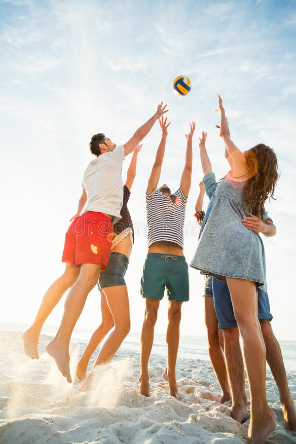 Friends trying to catch volley ball stock images