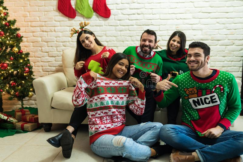 Friends In Ugly Sweater Celebrating Christmas Together At Home royalty free stock photo