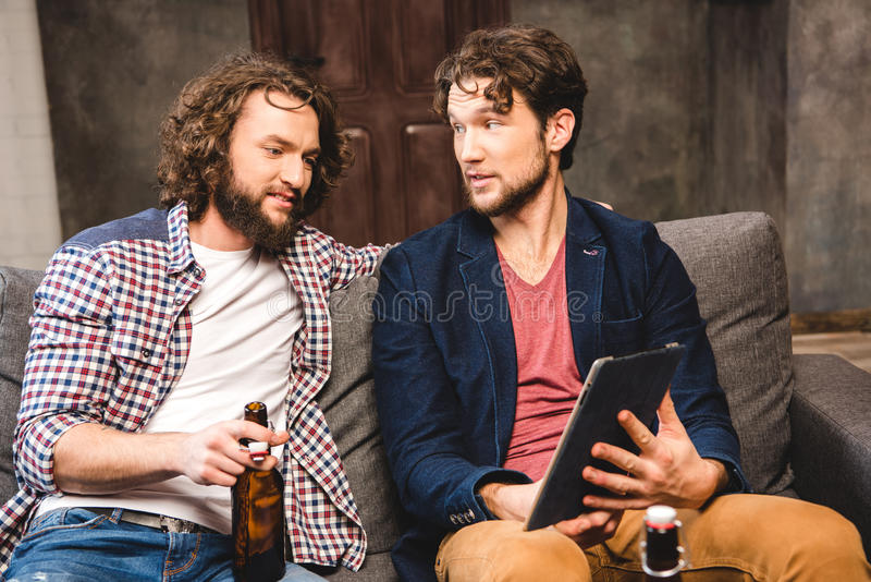 Friends using digital tablet. Smiling male friends sitting on sofa and using digital tablet stock images