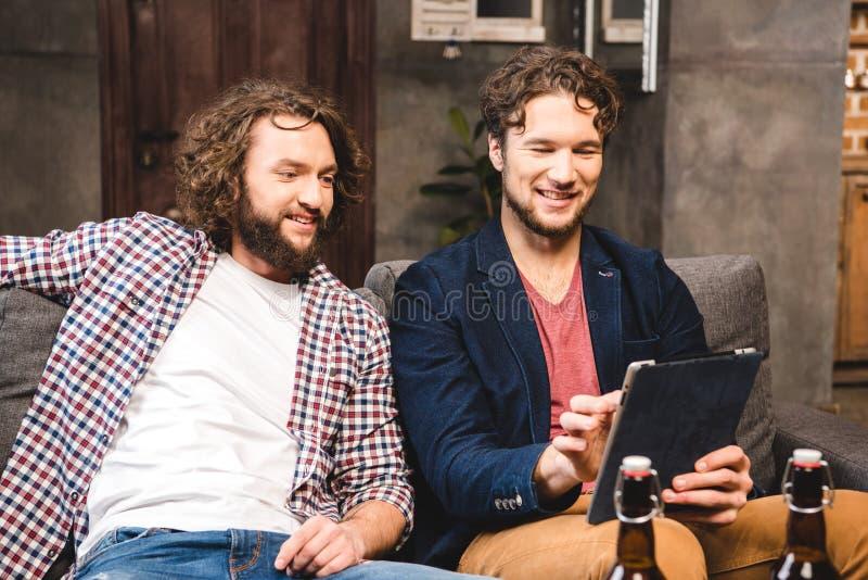 Friends using digital tablet. Smiling male friends sitting on sofa and using digital tablet stock image