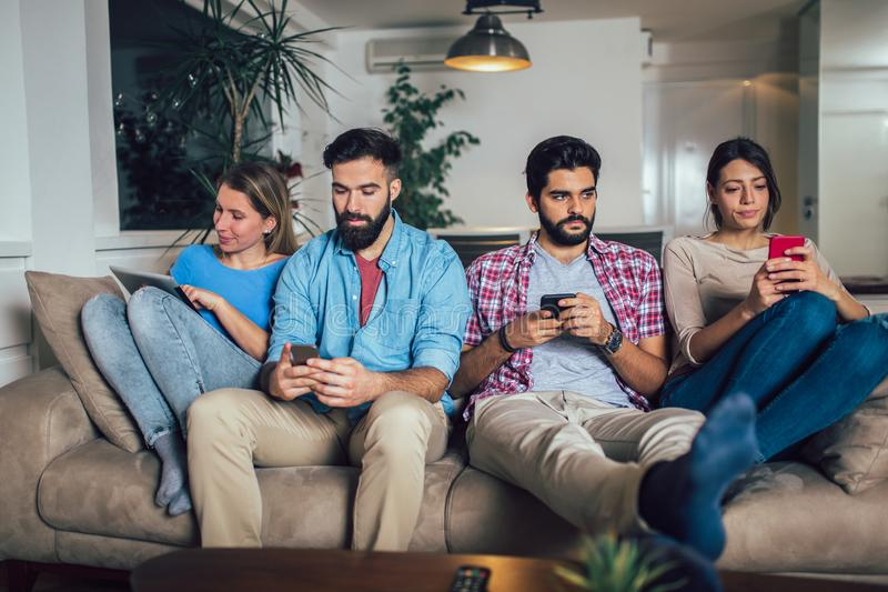 Friends using electronic devices while sitting on sofa. At home stock images