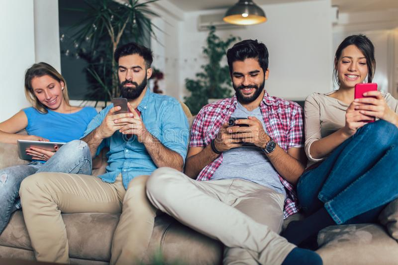Friends using electronic devices while sitting on sofa royalty free stock photography