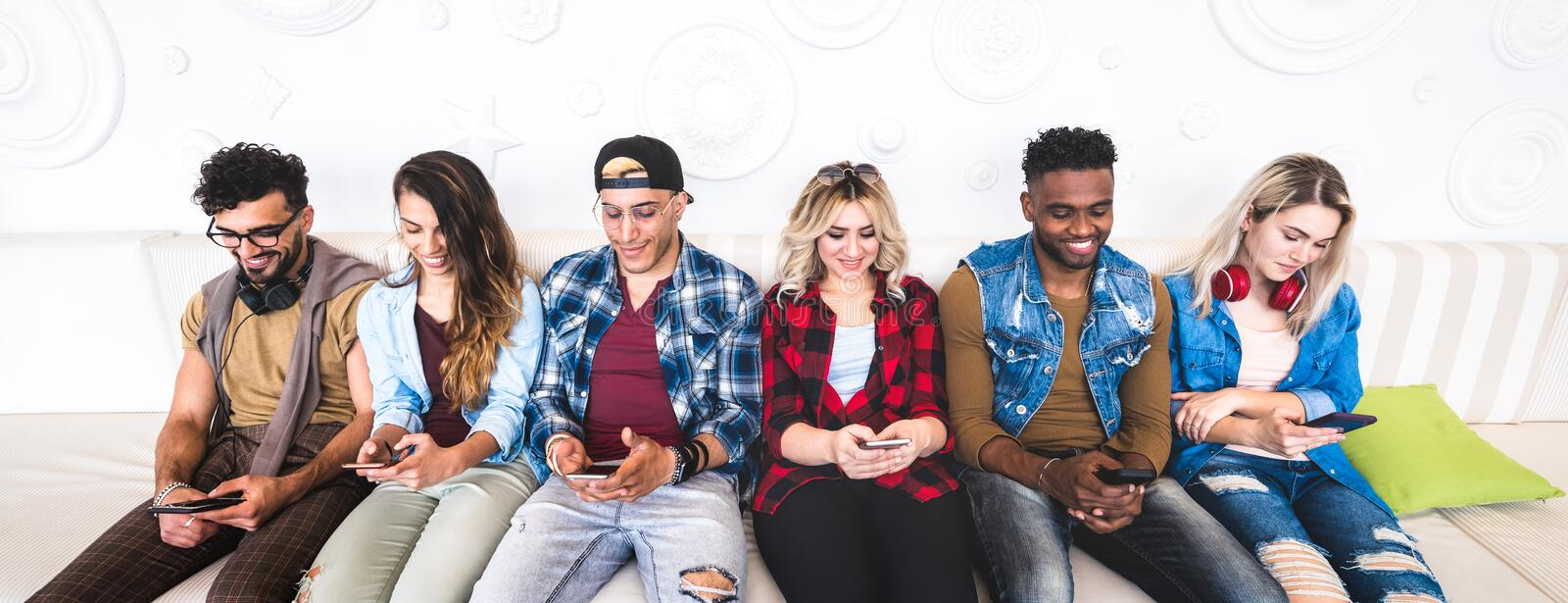 Friends using smartphone on sofa at indoor venue - People group addicted by mobile smart phone - Technology concept stock image