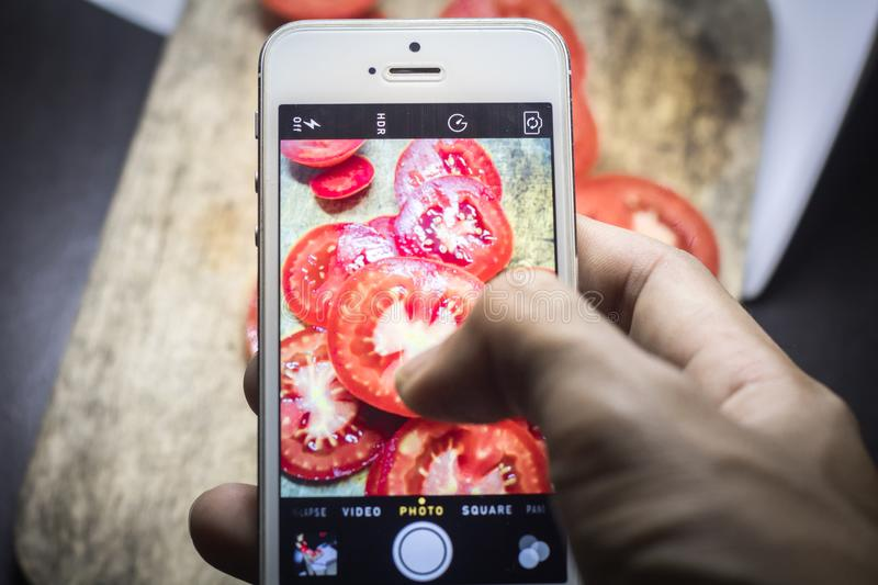 Friends using smartphones to take photos of food royalty free stock images