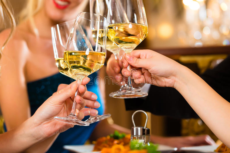 Friends in a very good restaurant clink glasses royalty free stock photos