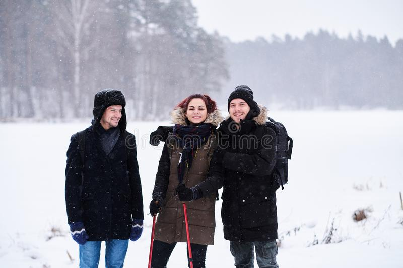 Friends walk in the cold snowy forest stand in a hug and look at the camera. Friends hiking in the cold snowy forest stand in a hug and look at the camera royalty free stock photos