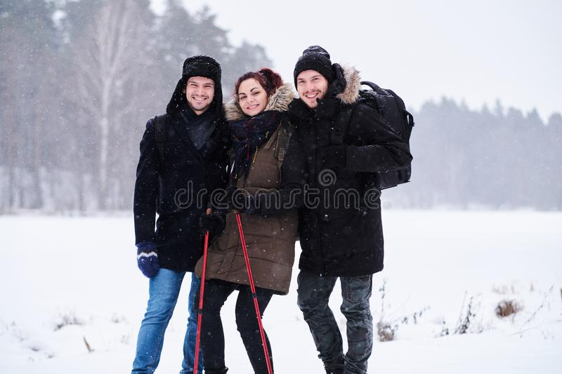 Friends walk in the cold snowy forest stand in a hug and look at the camera. Friends hiking in the cold snowy forest stand in a hug and look at the camera stock photos