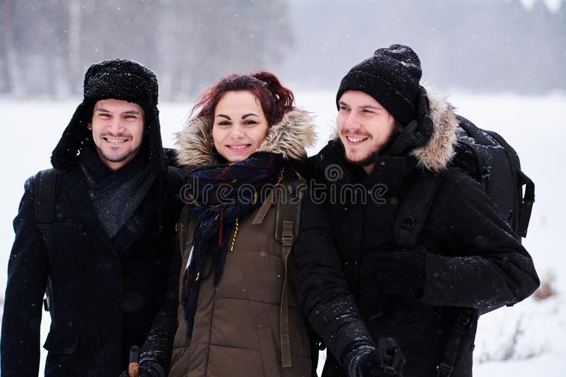 Friends walk in the cold snowy forest stand in a hug and look at the camera. Friends hiking in the cold snowy forest stand in a hug and look at the camera royalty free stock image