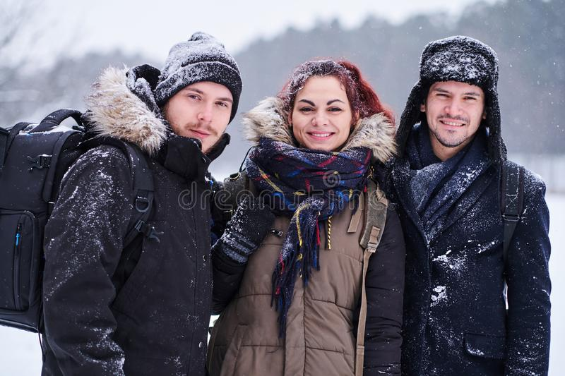 Friends walk in the cold snowy forest stand in a hug and look at the camera. Friends walk in the cold snowy forest stand in a hug and smiling while look at the royalty free stock photos