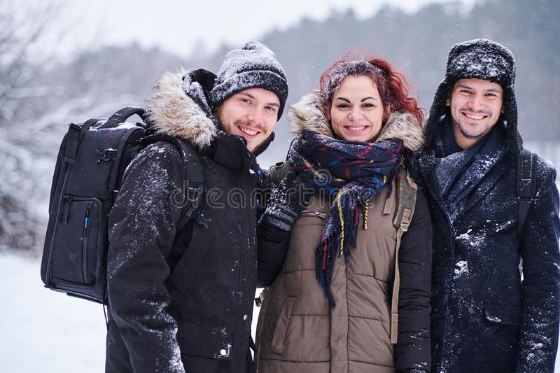 Friends walk in the cold snowy forest stand in a hug and look at the camera. Friends walk in the cold snowy forest stand in a hug and smiling while look at the stock images