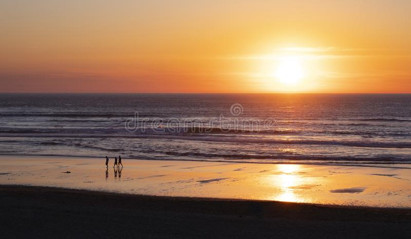 Friends walking on the beach at sunset royalty free stock photo