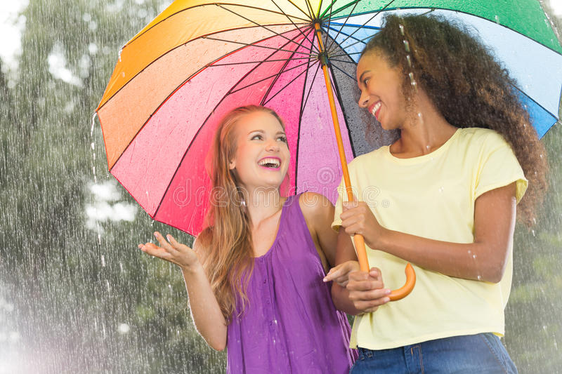 Friends walking with colorful umbrella stock photo