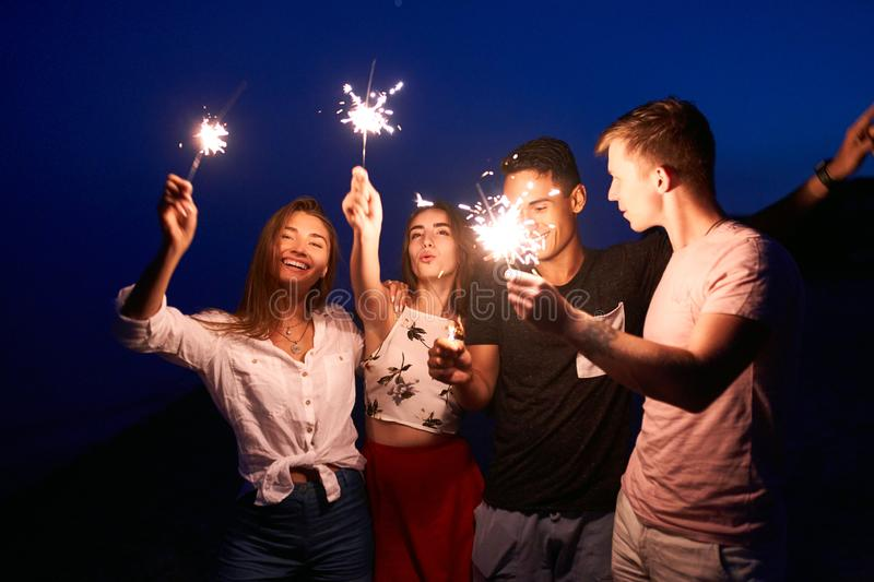Friends walking, dancing and having fun during night party at the seaside with bengal sparkler lights in their hands stock photo