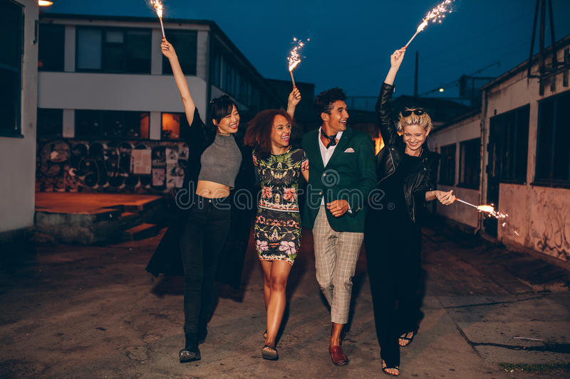Friends walking down the city street with firework. Full length shot of four young friends walking down the city street with fireworks and celebrating new years stock image