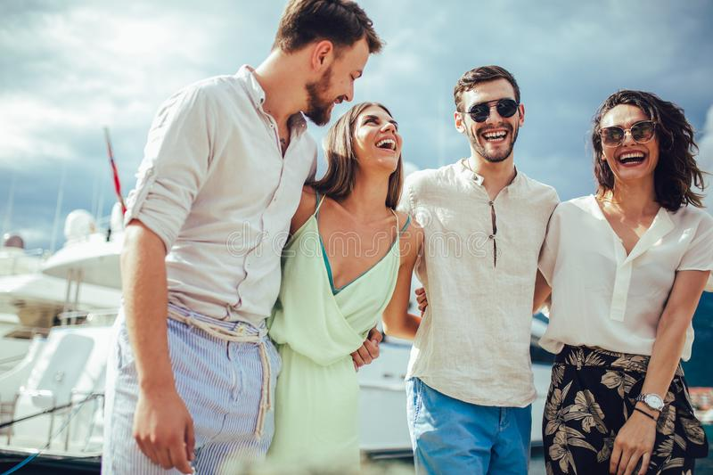 Friends walking by the harbor of a touristic sea resort stock photos