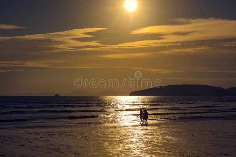 Friends Walking On Shore At Beach During Sunset royalty free stock photography