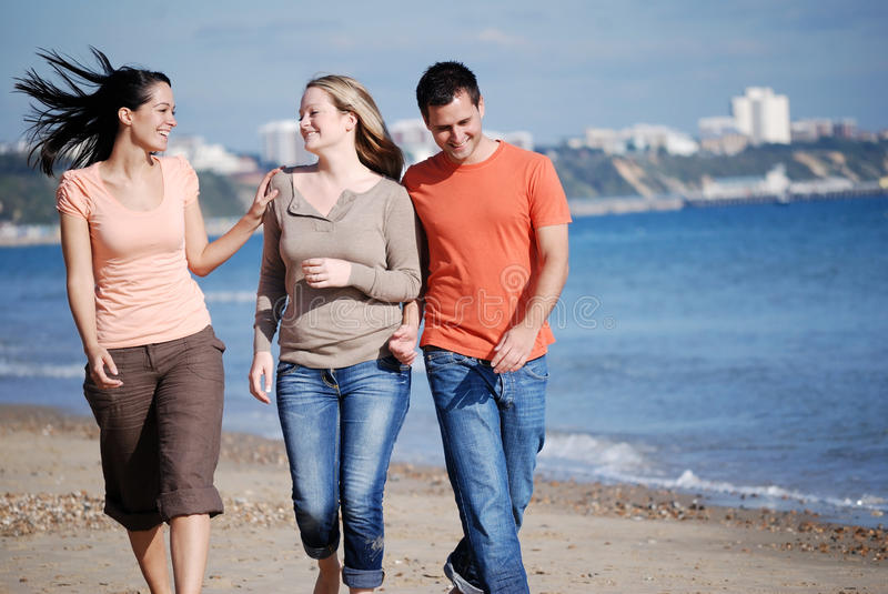 Friends walking together at the beach royalty free stock image