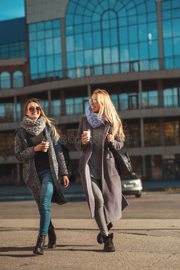 Friends walking together. Two beautiful women spend time on the street holding coffee and smiling. royalty free stock images