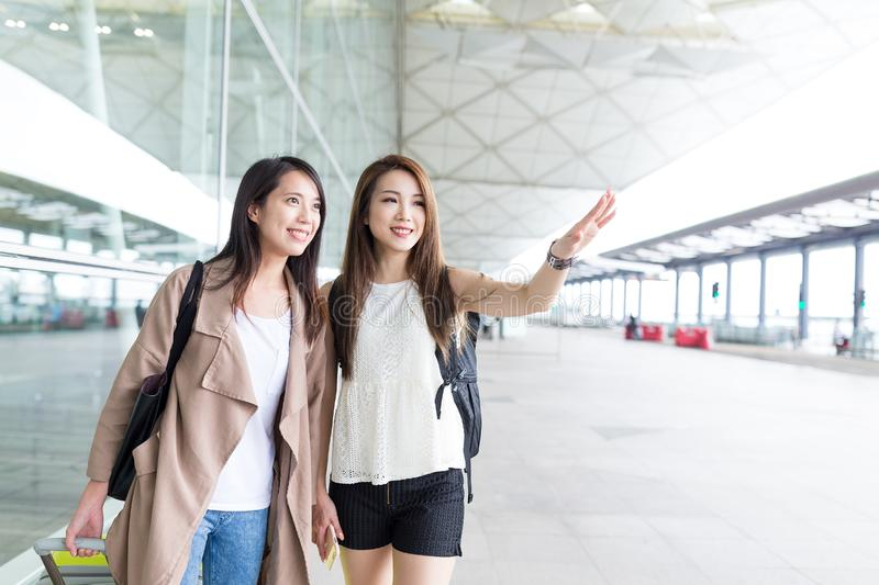 Friends wanting taxi in airport. Beautiful young asian woman stock image