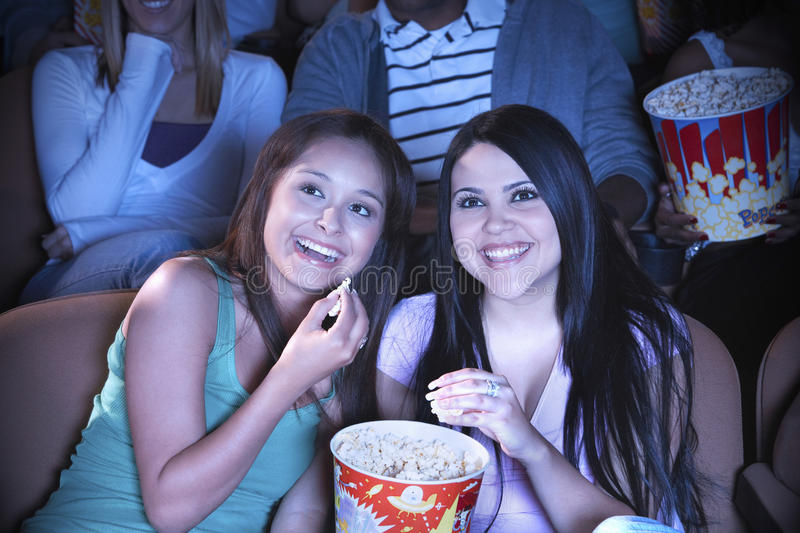 Friends Watching Film In Movie Theater. Young friends eating popcorn while watching film in movie theater stock photo
