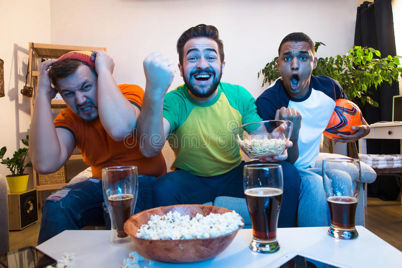 Friends watching football game. Picture of excited and amazed friends watching football game on TV. Handsome men screaming when someone kicking goal royalty free stock photos