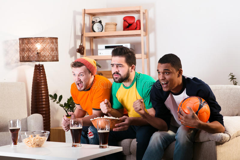 Friends watching football game. Picture of friends watching football game on TV while spending their weekends at home with alcohol drinks and pop corn. Football stock photography