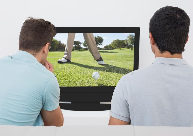 Friends watching golf on television at home stock photo