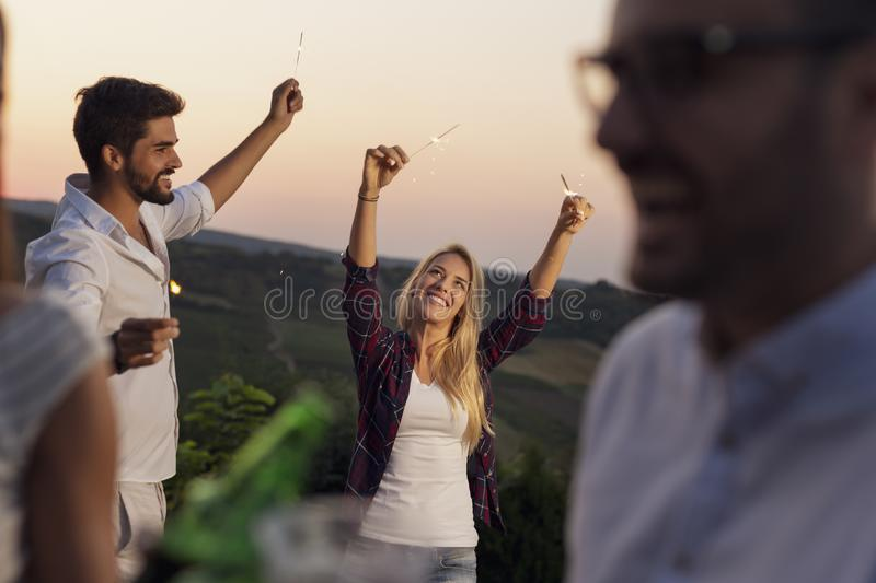 Friends waving with sparklers stock photos