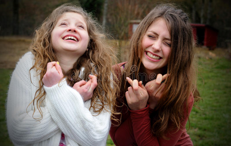 Friends Wishing Wishes. Two pretty young girls intensely just wishing and hoping with fingers crossed, both with long blond hair and smiling. Shallow depth of royalty free stock image